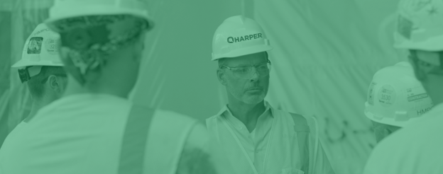Construction workers working in an office building wearing Limbach branded hard hats
